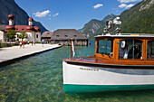 Excursion boat in front of baroque style pilgrimage church St Bartholomae, Koenigssee, Berchtesgaden region, Berchtesgaden National Park, Upper Bavaria, Germany