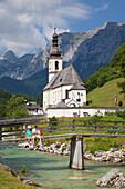 Father and children sitting on a pedestrian bridge over Ramsauer Ache in front of Ramsau church, view to Reiteralpe, Berchtesgaden region, Berchtesgaden National Park, Upper Bavaria, Germany