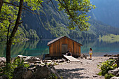 Young couple having a rest at a boat house at Obersee, Koenigssee, Berchtesgaden region, Berchtesgaden National Park, Upper Bavaria, Germany