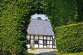 Half-timbered house behind a gate in a hedge of beeches, Monschau-Hoefen, Eifelsteig hiking trail, Eifel, North Rhine-Westphalia, Germany