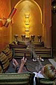 Woman enjoying a shisha pipe in the lounge area, Riad Anayela, Marrakech, Morocco