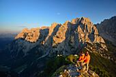 Two persons enjoying view from Stripsenkopf to mountain scenery, Zahmer Kaiser, Kaiser mountain range, Tyrol, Austria