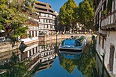 Timbered houses and a sightseeing boat on a canal in the quarter Petite France, Strasbourg, Alsace, France, Europe