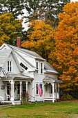 House with colorful tree in autumn in East Barnet, Vermont, USA