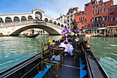 A masked couple in a gondola in front of the Rialto Bridge at the carnival in Venice, Italy, Europe