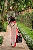 Vietnamese graduate wearing tradional dress Ao Dai at Temple of Literature, Hanoi, Vietnam