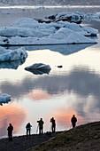 Photographers silhouette in Jökulsarlón glacial lagoon  Iceland