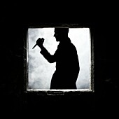 a man with a knife at a window of an old, abandoned house
