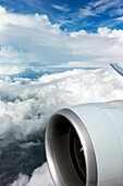 An aircraft engine and clouds out an airplane window