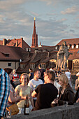 View across the old Main bridge to St. Mary's chapel, young people drinking wine at sunset, Wuerzburg, Franconia, Bavaria, Germany
