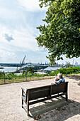Paar sitz auf einer Parkbank in den Altonaer Terrassen und schaut auf den Hamburger Hafen, Hamburg, Deutschland