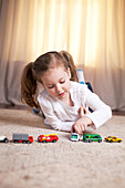 Girl Playing on Floor with Toy Cars and Trucks