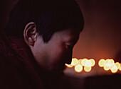 Tibetan Nun Praying with Candles in Background, Nangchen, Eastern Tibet