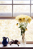 Bouquet of Yellow Flowers in Vase Next to Horse Sculpture, and Blue Creamer