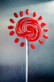 Red Lollipop Surrounded by Red Jellybeans on Metal Background