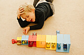 Young Boy Playing with Boxes and Toy Cars