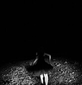 Young Woman in Dress Running Across Lawn at Night, Rear View