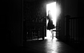 Woman in Dress Standing in Illuminated Doorway to Dark Dining Room