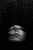 Young Woman Looking Up into Darkness, Close-Up of Face