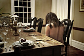Ghost-Like Nude Young Woman Sitting at Dining Room Table, Rear View