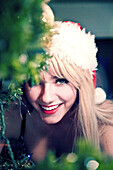 Smiling Young Woman in Santa's Hat Peeking Around Christmas Tree Branches