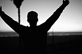 Man Holding Arms Up at Beach, Close-Up, Silhouette, Rear View