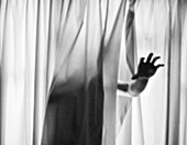 Hand Reaching out from Curtains
