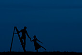 Man Standing on Ladder While Holding Woman's Hand, Silhouette