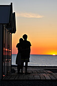 Couple On The Beach Embracing Near Beach Huts At Sunset, Boardwalk Of Cayeux-Sur-Mer, Bay Of Somme, Somme (80), France