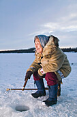 Elder Native Yupik Female Sits On Stump Ice Fishing Kuskokwim River Tuluksak Western Alaska Winter