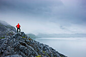 A Lone Hiker Stands On A Rocky Outcropping Overlooking Shoup Bay On A Cloudy Day, Shoup Bay State Marine Park, Prince William Sound, Southcentral Alaska