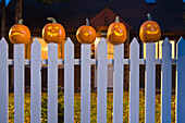 Jack-O-Lantern Faces Stuck On Top Of The Fence Boards Of White Picktet Fence With A House In Background At Twilight During Fall In Anchorage, Alaska.