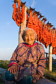Elder Native Yupik Woman Sits In Front Of Salmon Drying On Rack Kuskokwim River @ Sunset We Alaska