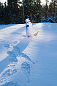 Snowman Walking W/Snowshoes Leaving Tracks In Snow Drift Late Afternoon Alaska Winter