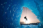 Composite: View From Inside An Ice Cave Of An Iceberg Frozen In Mendenhall Lake As An Ice Climber Rappels Down A Rope, Juneau, Southeast Alaska, Winter