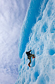 An Ice Climber Ascends The Face Of A Large Iceberg Frozen Into Mendenhall Lake, Juneau, Southeast Alaska, Winter