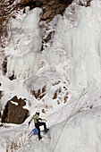 Female Ice Climber Rappels Down An Ice Wall Next To The Seward Highway, Southcentral Alaska, Winter
