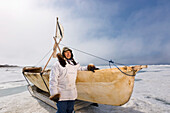 Male Inupiaq Eskimo Hunter Standing Beside An Inupiaq Umiaq Made Of Bearded Seal Skin (Ugruk) While Wearing A Traditional Eskimo Parka (Atigi) And Seal Skin Hat, Chukchi Sea Near Barrow, Arctic Alaska, Summer