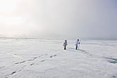 Two Inupiaq Eskimo Hunters Wearing Their Eskimo Parka's (Atigi) Carry A Rifle And Walking Stick While Walking Over The Shore Ice Along The Chukchi Sea, Barrow, Arctic Alaska, Summer
