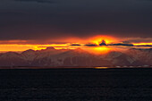 'A Colourful Sunset Below A Cloud Bank Over The Chugach Mountains Turns Into A Surreal Golden Glow During Low Tide On The Copper River Flats Salmon Fishing Grounds; Cordova Alaska United States Of America'