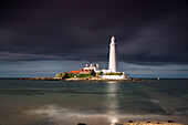 'White Lighthouse Illuminated By Sunlight Under A Dark Stormy Sky; St. Mary's Island Northumberland England'