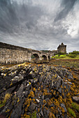 'An Old Stone Bridge Leading Towards Old Stone Buildings Under A Cloudy Sky; Kyle Of Lochalsh Scotland'