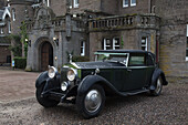 'Vintage Black Car Parked Outside A Large Home; Perthshire Scotland'