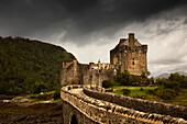 'Stone Bridge Leading To A Castle Under A Stormy Sky; Kyle Of Lochalsh Highlands Scotland'