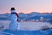 'Snowman in front of downtown skyline at dawn knik arm and chugach mountains in the background;Anchorage alaska usa'