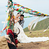 'China, Xizang, Tibet, Bride And Groom Posing Under Prayer Flags Flying In Wind; Shannan'