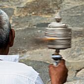 'China, Xizang, Man Holding Prayer Wheel; Tibet'