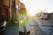 'Mexico, Guanajuato, Portrait Of Woman Walking Down Cobblestone Street With Sun Flare In Shot; San Miguel De Allende'