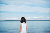 'Young Girl In White Top Facing A River;Saint-Simeon Quebec Canada'
