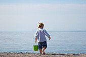 'Young Boy Carrying A Pail On The Beach By Lake Ontario;Ontario Canada'